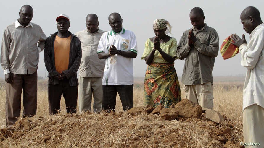 FILE - People gather around a grave, where three murdered family members were buried together, in Jos, in Nigeria's Plateau state, December 28, 2011, following clashes between farmers and herders.