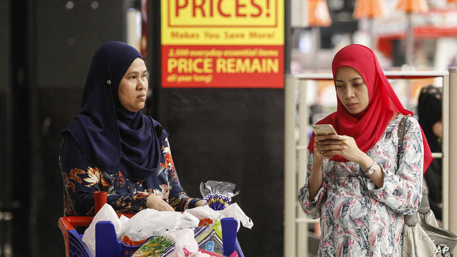 FILE - A Malaysian Muslim woman checks her mobile phone while shopping at a mall outside Kuala Lumpur, Malaysia, Aug. 18, 2015.