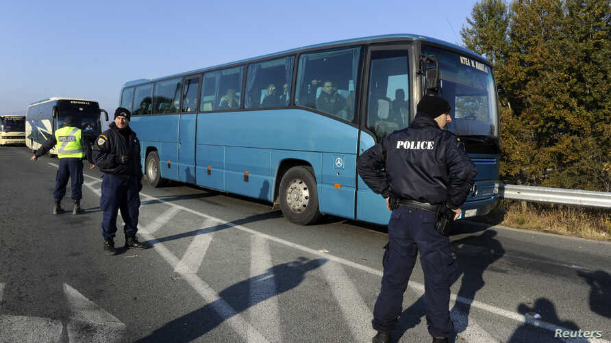 Greek police officers direct buses carrying hundreds of migrants, who were stranded on the Greek-Macedonian border and blocked rail traffic, after a police operation near the village of Idomeni, Greece, Dec. 9, 2015.