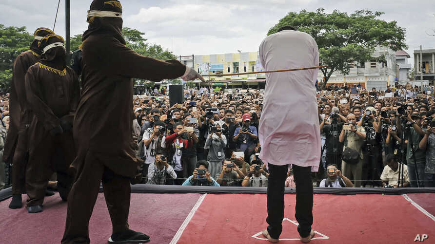 Shariah law official whips one of two men convicted of gay sex during a public caning outside a mosque in Banda Aceh, Aceh province, Indonesia, May 23, 2017.