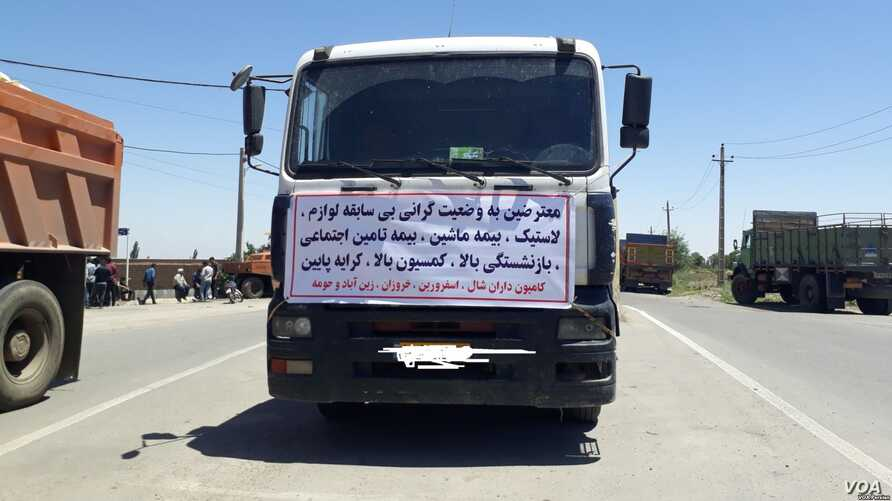 "A truck in the northern Iranian city of Qazvin displays a sign of a striking trucker driver on May 28, 2018. The sign reads: ""We are protesting the unprecedented high prices for spare parts and tires..."""