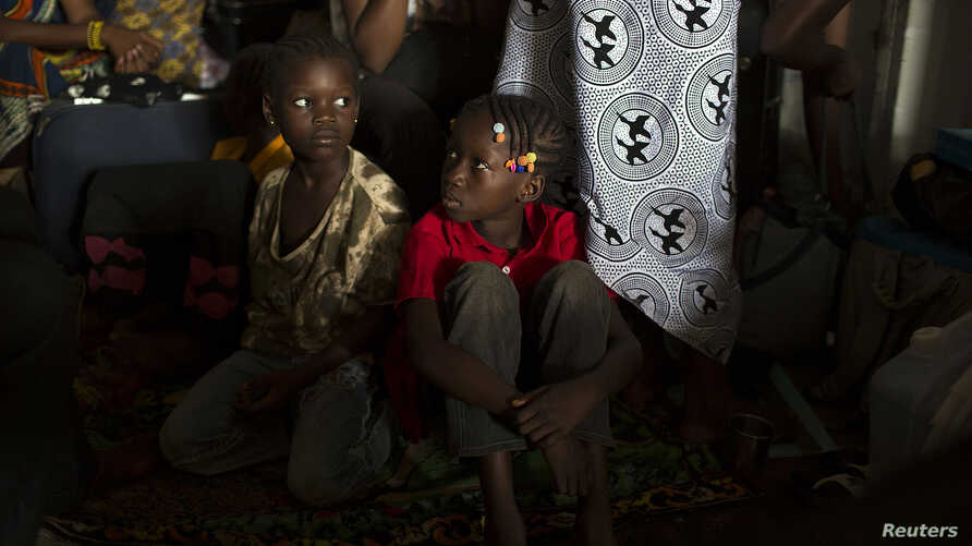 FILE - Children sit inside a container truck as they wait to depart to the west of the country towards the border with Cameroon, in a convoy escorted by African Union (AU) peacekeeping forces as they flee sectarian violence in the capital Bangu.