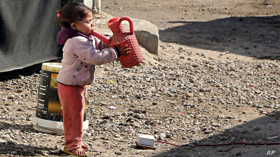 FILE - A girl drinks water in the street outside her tent at a camp for internally displaced people in western Baghdad, Iraq, Feb. 1, 2018.