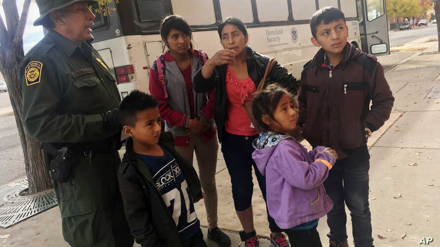 FILE -  A migrant family from Central America waits outside the Annunciation House shelter in El Paso, Texas, after a U.S. Immigration and Customs Enforcement officer drops them off, Nov. 29, 2018.