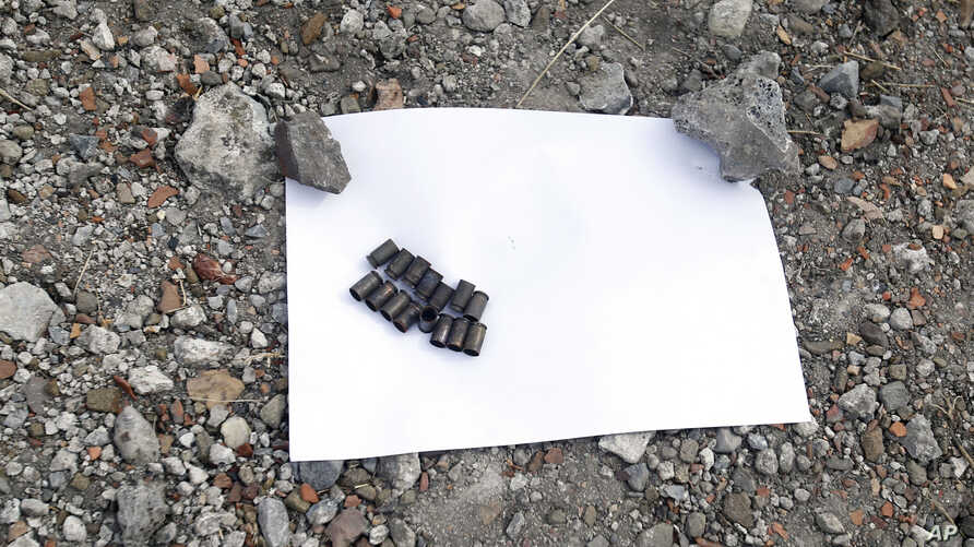 Bullet casings are seen in front of a mass grave near a local mine in the village of Nyzhnya Krynka, eastern Ukraine, Sept. 23, 2014.