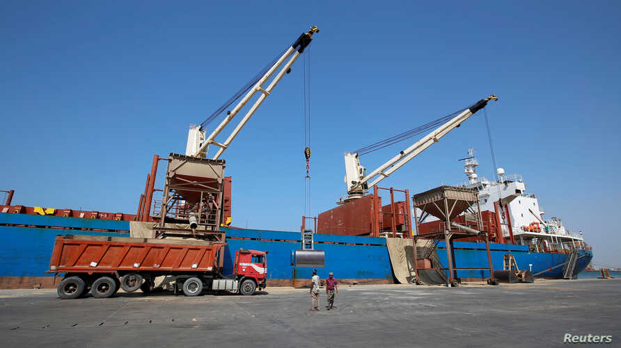 FILE - Workers unload aid shipment of wheats from St. George ship, at the Red Sea port of Hodeidah, Yemen Nov. 30, 2017.