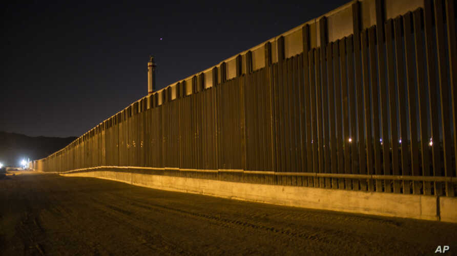 FILE - A portion of the new steel border fence stretches along the US-Mexico border in Sunland Park, New Mexico, March 30, 2017.