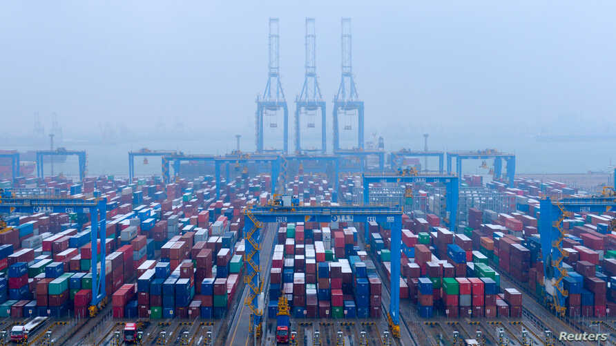 FILE - Containers and trucks are seen on a snowy day at an automated container terminal in Qingdao port, Shandong province, China, Dec. 10, 2018,