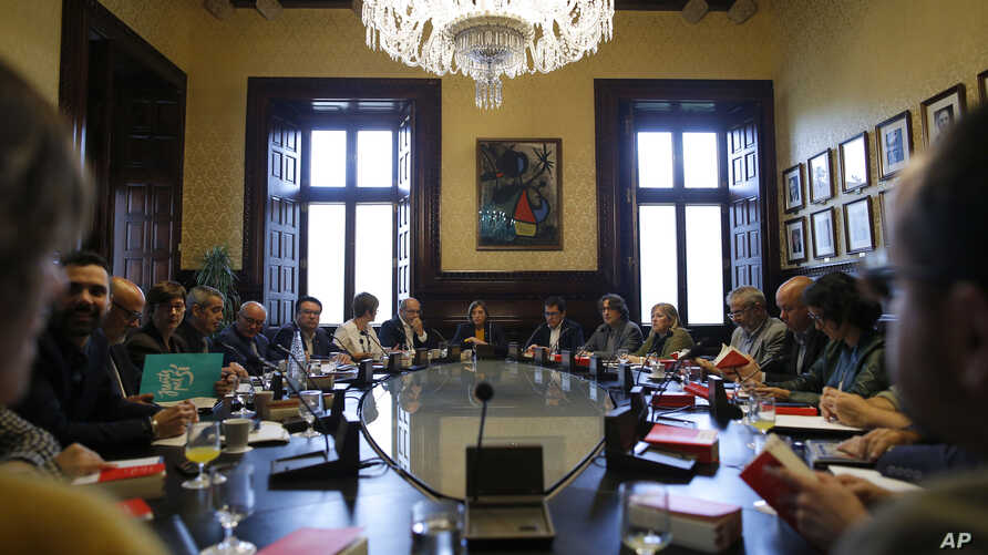 President of the Catalan parliament Carme Forcadell, center, sits with parliament representatives to discuss their next move after Spanish government announced plans to remove members of the region's pro-independence government, at the Catalonia Parl