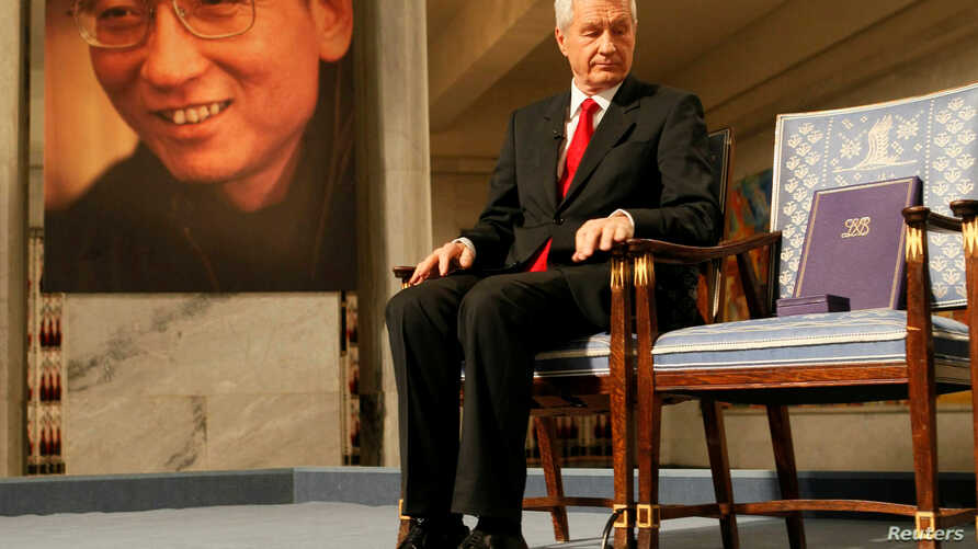 Chairman of the Norwegian Nobel Committee Thorbjoern Jagland looks down at the Nobel certificate and medal on the empty chair where this year's Nobel Peace Prize winner jailed Chinese dissident Liu Xiaobo would have sat, as a portrait of Liu is seen