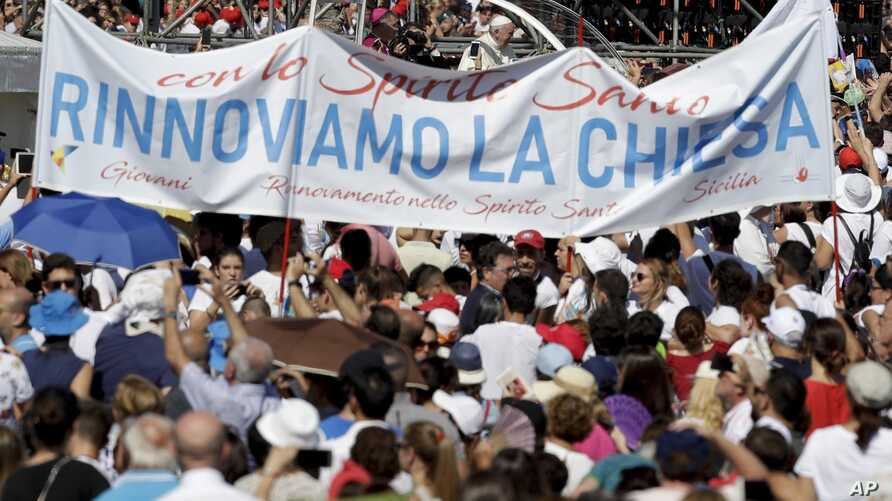 """Pope Francis is driven through the crowd as a large banner reading """"Let's renew the church"""" is visible in the foreground, in Palermo, Italy, Sept. 15, 2018. Francis was paying tribute in Sicily to a priest who worked to keep youths away from the Mafi"""