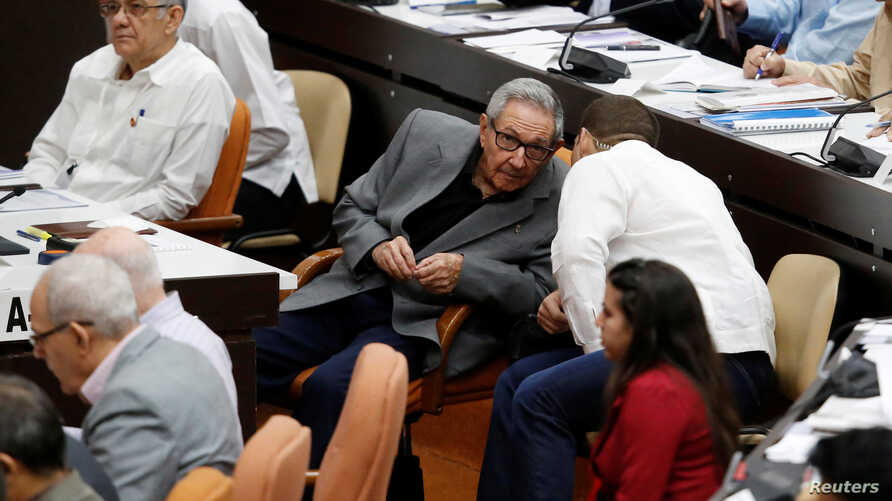 Cuba's former President Raul Castro, center left, talks to his grandson and bodyguard Raul Rodriguez Castro during a session of the National Assembly in Havana, Dec. 21, 2018.