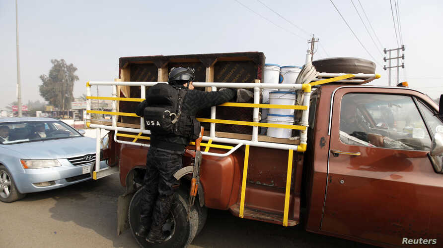 A police officer searches a vehicle at a checkpoint as security increases after a bomb attack, at Abu Ghraib district in west of Baghdad, Jan. 9, 2014.