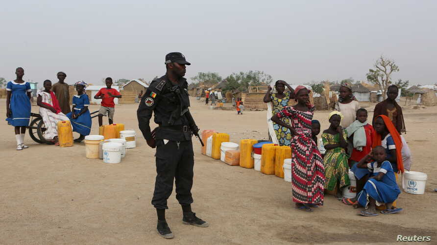 FILE - A Cameroonian police officer enforces order in Minawao, Cameroon, March 15, 2016.