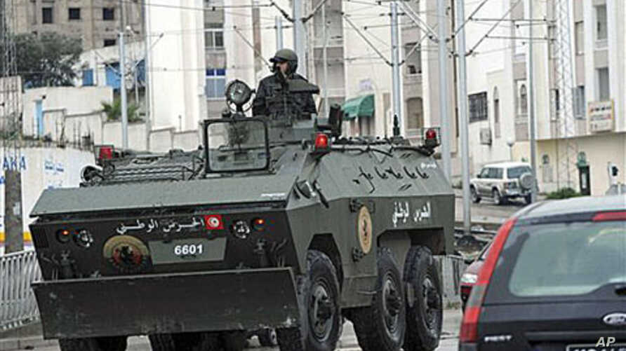 A soldier drives an armored vehicle through Ettadhamoun, west of Tunis, where riots reportedly took place, Jan 12, 2011