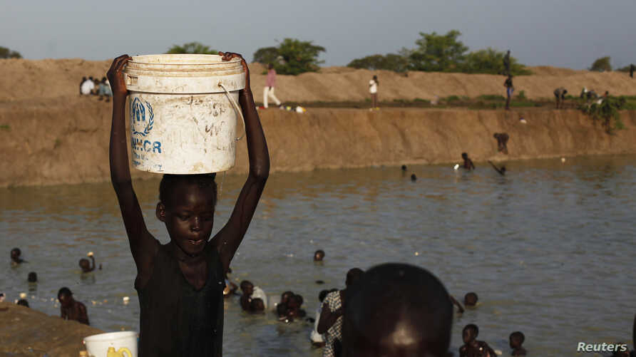 FILE - A girl carries a bucket filled with water from a pond in a camp for internally displaced persons at the United Nations base in Bentiu, Unity State, South Sudan.