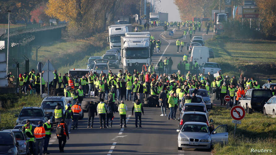 People wearing yellow vests, a symbol of a French drivers' nationwide protest against higher fuel prices, block the Paris-Brussels motorway in Haulchin, France, Nov. 17, 2018.