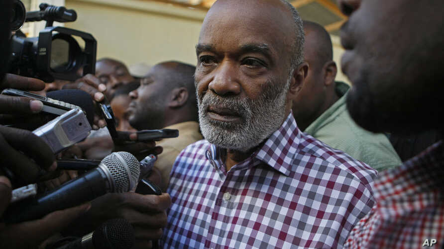FILE - Haiti's President Rene Preval, center, speaks to the press after casting his vote for presidential elections at a polling station in Port-au-Prince.