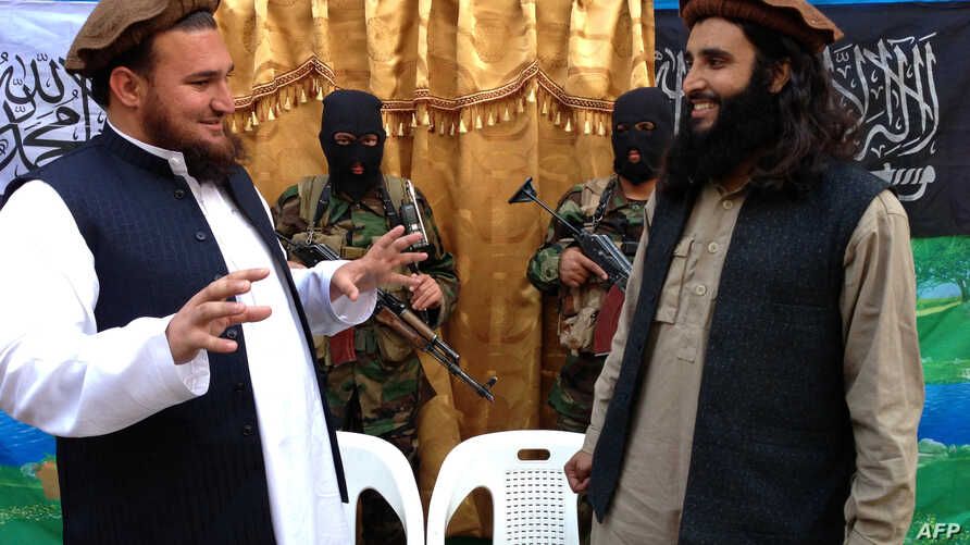 Tehreek-e-Taliban Pakistan (TTP) spokesman Ehsanullah Ehsan (L) talks with new TTP member Adnan Rasheed following a press conference in Shabtoi, a village in Pakistan's South Waziristan, on February 2, 2013.
