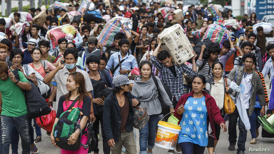 FILE - Cambodian migrant workers carry their belongings as they walk to cross the border at Aranyaprathet in Sa Kaew, June 15, 2014.