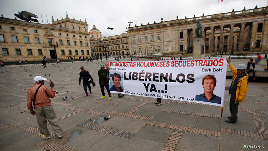 """People protest against the kidnapping of Dutch journalists Derk Johannes Bolt and Eugenio Ernest Marie in Bogota, Colombia, June 21, 2017. The banner reads: """"Dutch journalists kidnapped, Liberty Now."""" Bolt and Marie were released by ELN rebels, June"""