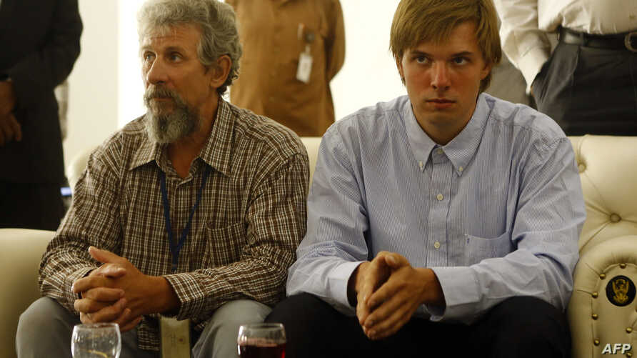Sergei Cherepanov, left, and Mikhail Antyufeev, two Russians kidnapped in Sudan's Darfur region in January 2015, wait at the airport in the Sudanese capital, Khartoum, after they were freed by their captors, June 6, 2015.