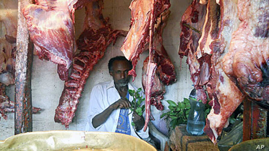 """Adam Mohamad, a butcher is not a """"hyena man,"""" but like many Hararis, he feels close to the animals and will feed them by hand if they come to his shop."""
