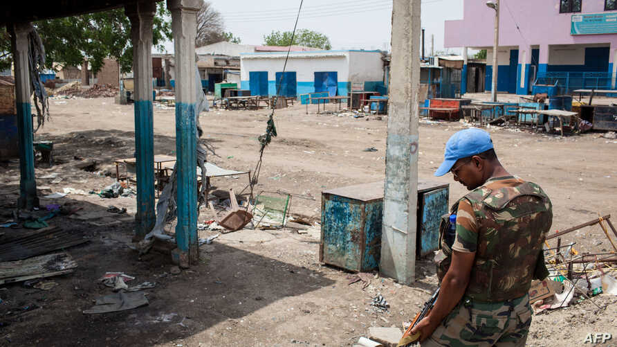 A United Nations peacekeeper looks at the destruction in downtown Malakal, on March 4, 2014.