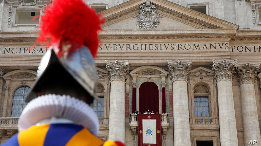 "A Swiss Guard stands as Pope Francis delivers his ""Urbi et Orbi"" (to the city and the world) message from the balcony overlooking St. Peter's Square at the Vatican, Dec. 25, 2016."
