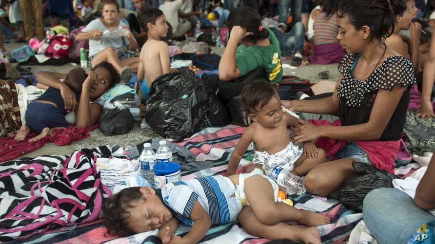 A group of migrants rests at the central park in Ciudad Hidalgo, Mexico, Oct. 20, 2018.