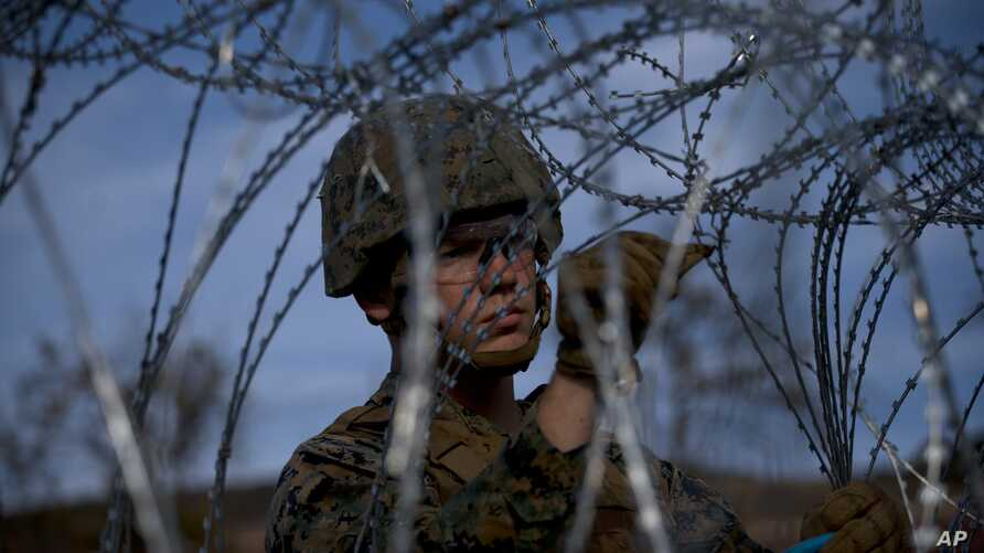 A soldier agent sets up barbed wire at the San Ysidro port of entry, at the U.S.-Mexico border, seen from Tijuana, Mexico,  Nov. 22, 2018.