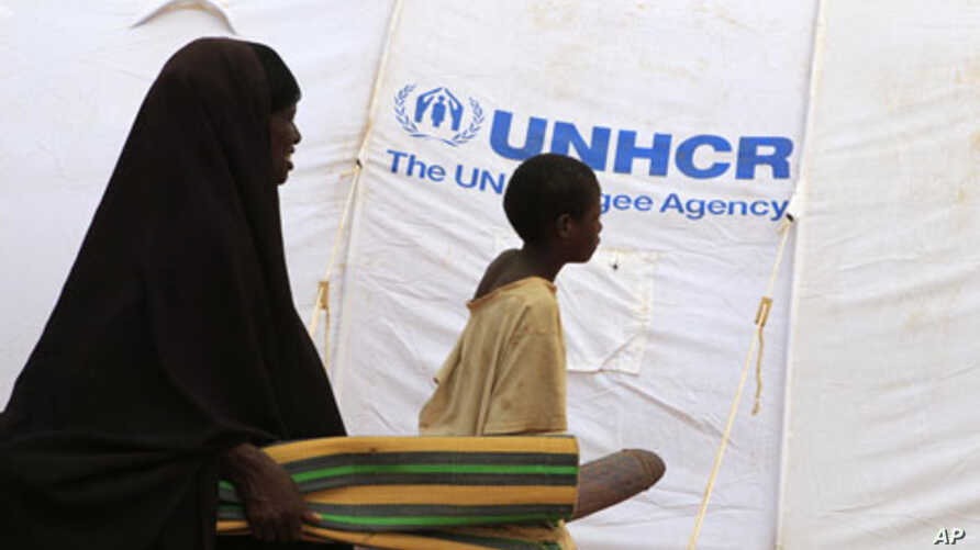 A newly arrived refugee family walks into Baley settlement near the Ifo extension refugee camp in Dadaab, near the Kenya-Somalia border, July 27, 2011