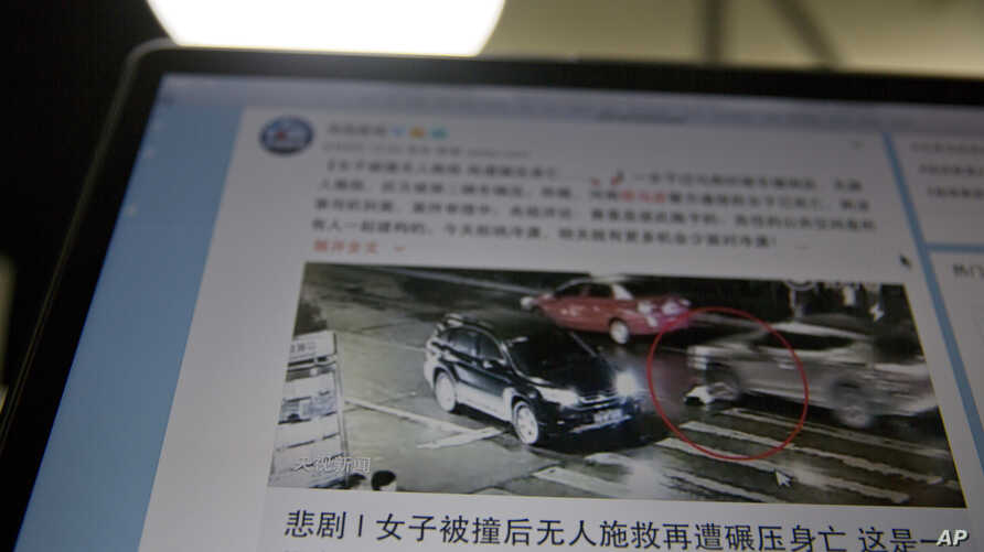 A website shows a frame from a video of a woman as she is run over by a car in Beijing, China. The initial reaction to the video among Chinese was outrage at the more than 40 pedestrians and drivers who failed to offer help.