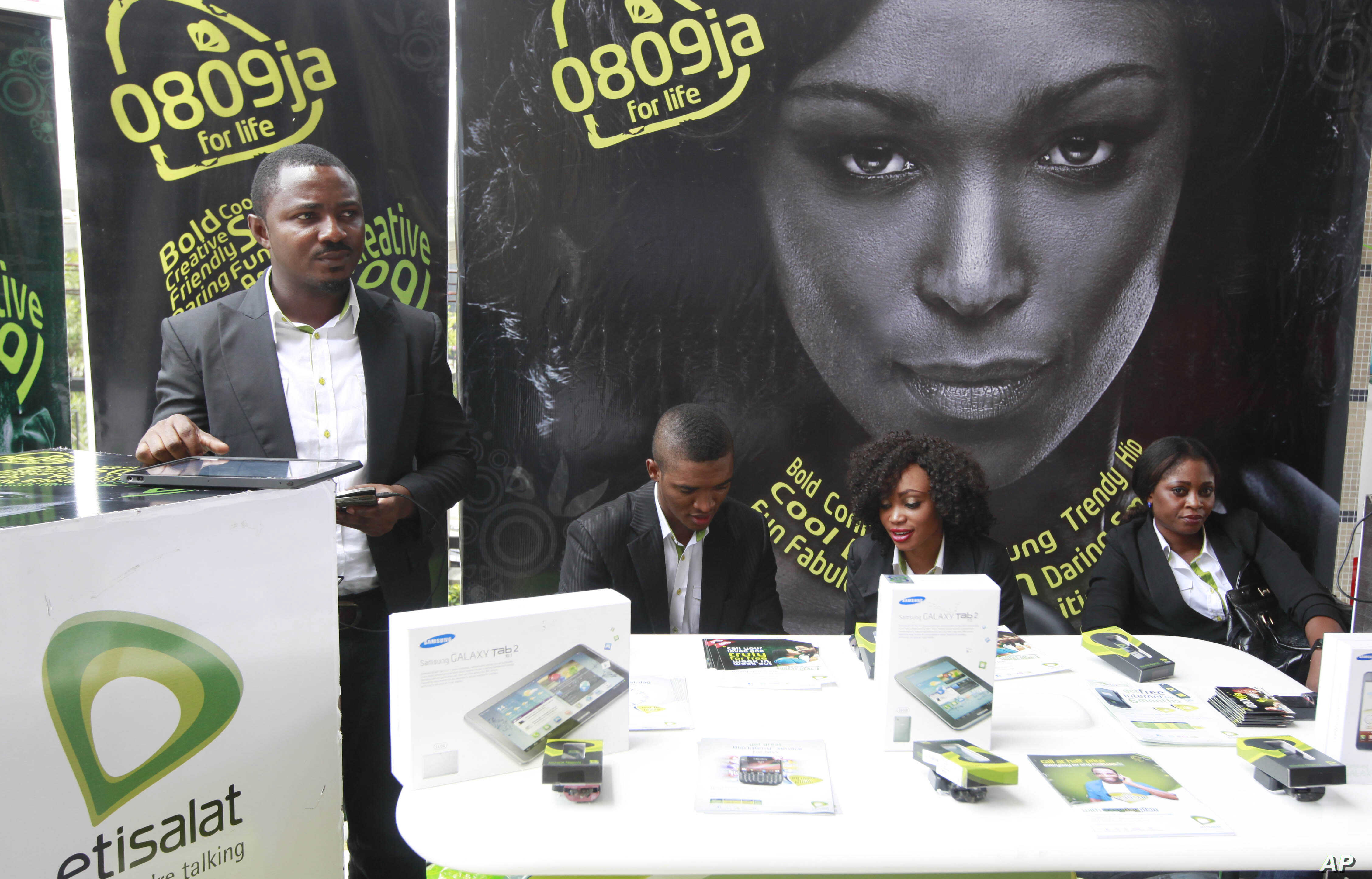 FILE - Staff of Internet and smartphone service provider Etisalat Nigeria wait for customers at a promotional stand in Lagos, Nigeria.