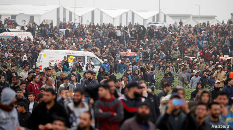 Palestinians are seen gathered during a protest marking Land Day and the first anniversary of a surge of border protests, at the Israel-Gaza border fence east of Gaza City, March 30, 2019.