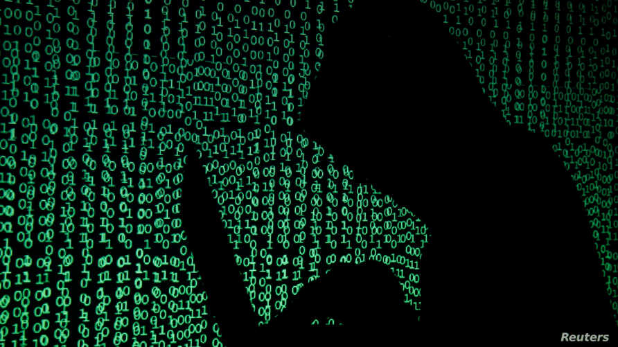 A hooded man holds a laptop computer as cyber code is projected on him in this picture taken on May 13, 2017.