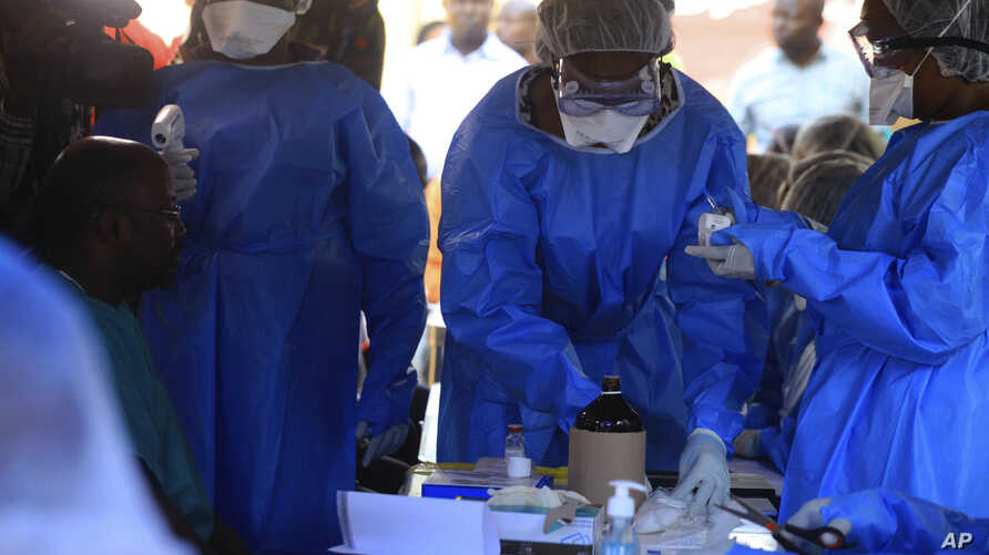 Healthcare workers from the World Health Organization prepare to give an Ebola vaccination to a front line aid worker in Beni Democratic Republic of Congo, Friday, Aug 10, 2018.