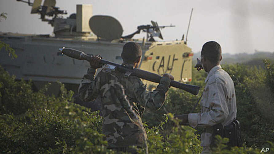 A Somali National Army soldier points at an African Union Mission in Somalia (AMISOM) armored personnel carrier during an advance into insurgent al-Shabab territory in Mogadishu, January 21, 2012.