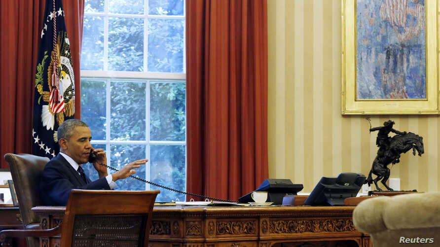 FILE - President Barack Obama is photographed through the window as he speaks in the Oval Office during a conference call at the White House in Washington, June 2, 2014.