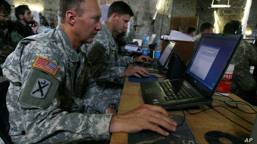 FILE - US soldiers monitor battlefield conditions at a joint military command center. Many experts say U.S.-Russian military cooperation in Syria is fraught with risks but they see few alternatives.