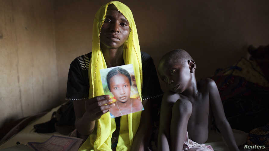 Rachel Daniel, 35, holds up a picture of her abducted daughter Rose Daniel, 17, as her son Bukar, 7, sits beside her at her home in Maiduguri, Nigeria, May 21, 2014.