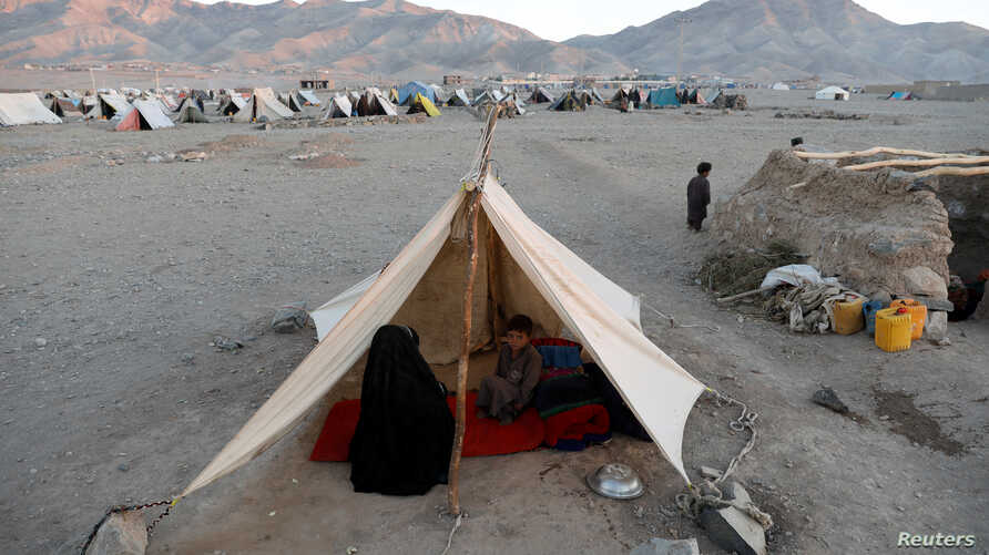FILE - Internally displaced Afghan family sits inside a tent at a refugee camp in Herat province, Afghanistan, Oct. 14, 2018.