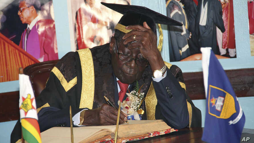 In this Friday Oct. 2, 2015 photo, Zimbabwean President Robert Mugabe writes his comments in a visitors' book at the University of Zimbabwe in Harare.