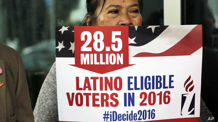 Georgina Arcienegas holds a sign in support of Latino voters during a protest outside the office of Florida Rep. Carlos Trujillo, Jan. 12, 2016, in Doral, Fla.