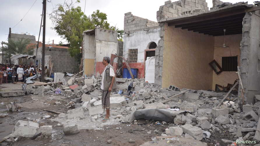 FILE - A man stands on the wreckage of a house destroyed by a Saudi-led air strike in Yemen's Red Sea port city of Houdieda, Dec. 21, 2015.
