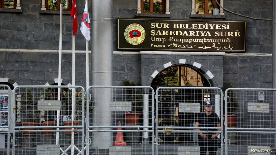 A riot police officer stands guard in front of Sur municipality office, following the removal of the local mayor from office after he was deemed to support Kurdish militants, in Diyarbakir, Turkey, September 11, 2016.