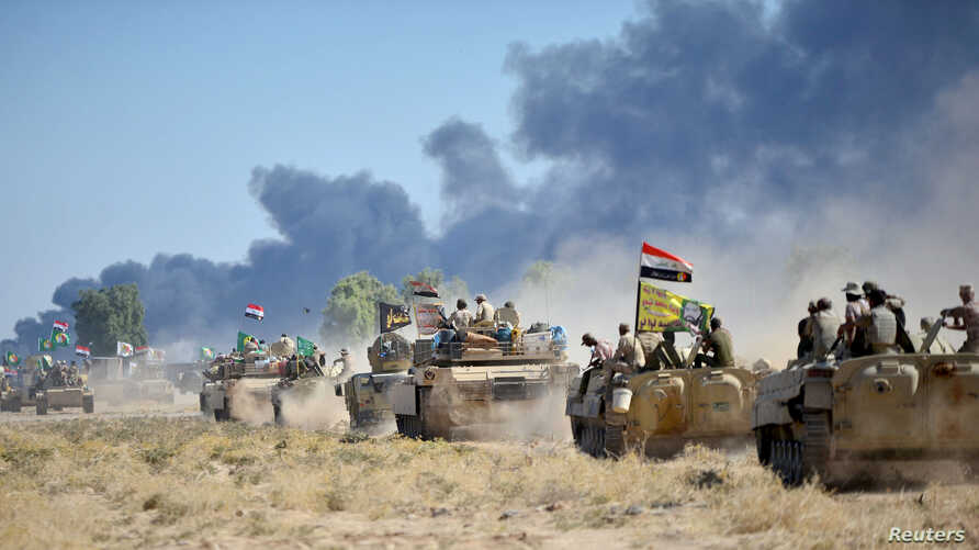 Shiite Popular Mobilization Forces (PMF) and the Iraqi army drive armored vehicles on the outskirts of Hawija, Iraq, Oct. 4, 2017.