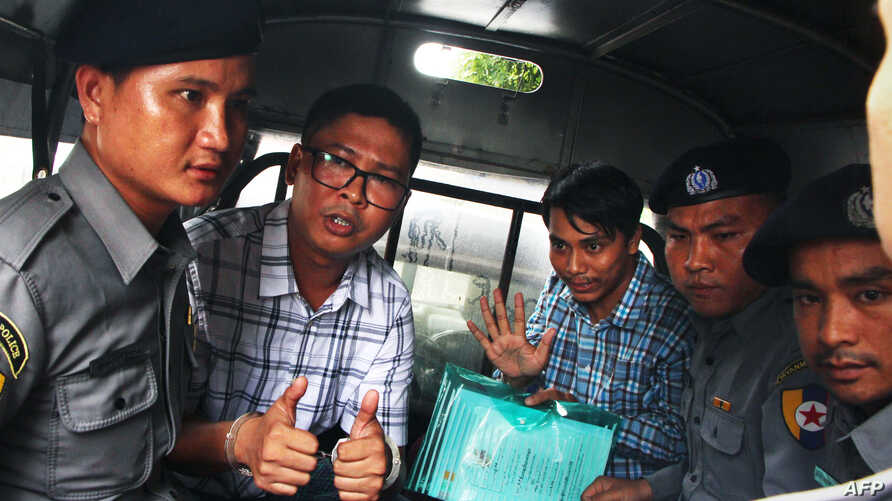 Detained Myanmar journalists Wa Lone, (L) and Kyaw Soe Oo (3rd-R) are escorted by police from the courthouse as they are taken to prison after the first day of trial in Yangon, July 16, 2018.