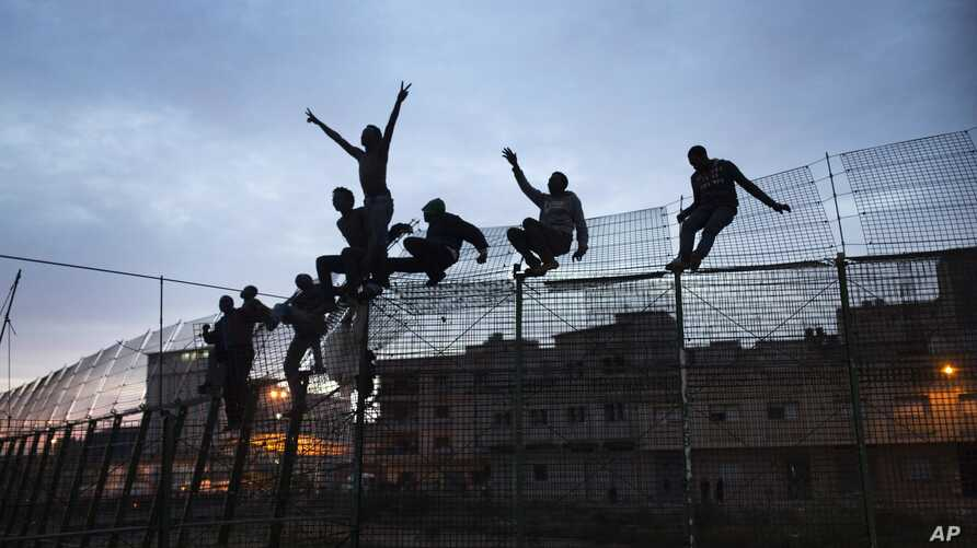 FILE - Sub-Saharan migrants climb over a metallic fence that divides Morocco and the Spanish enclave of Melilla, March 28, 2014.