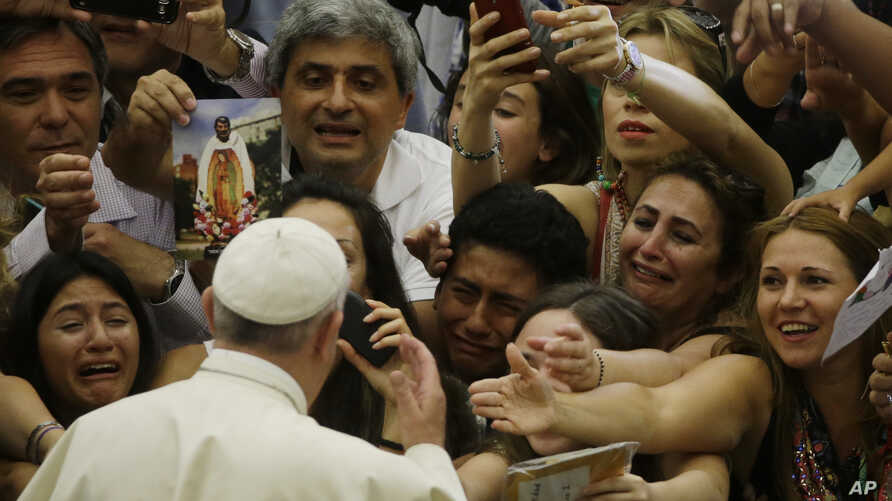 Pope Francis is cheered by faithful as he arrives in the Paul VI hall at the Vatican, Aug. 5, 2015.
